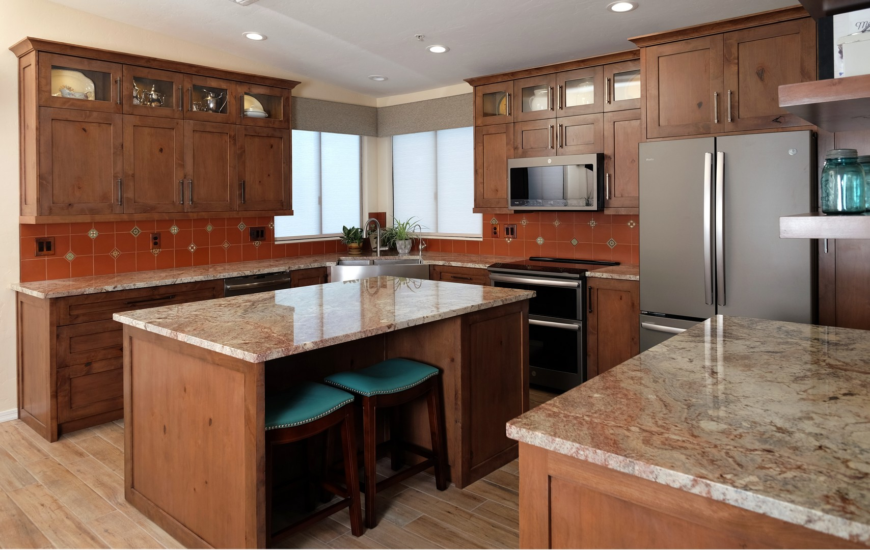 Tucson Southwestern kitchen design and remodel with Spanish Colonial Revival style featuring Mexican deco and terra cotta tiles, knotty custom cabinetry, and teal & turquoise accents.