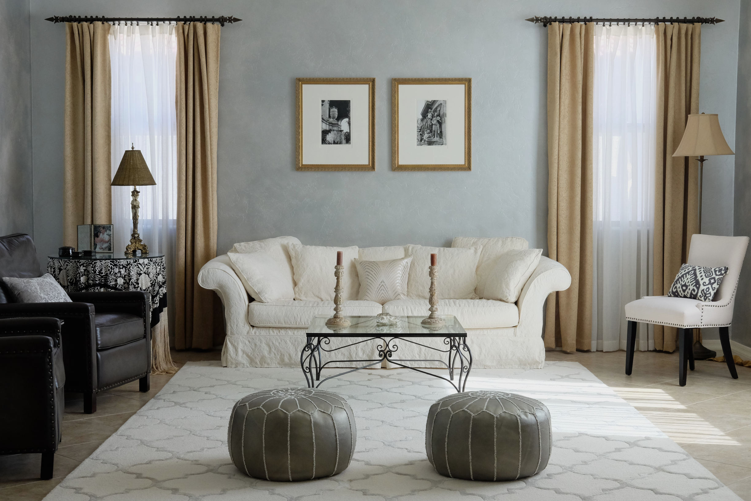Tucson interior design featuring Old Hollywood glamour style living room with Moroccan poufs, arabesque area rug, and Spanish Colonial wrought iron table
