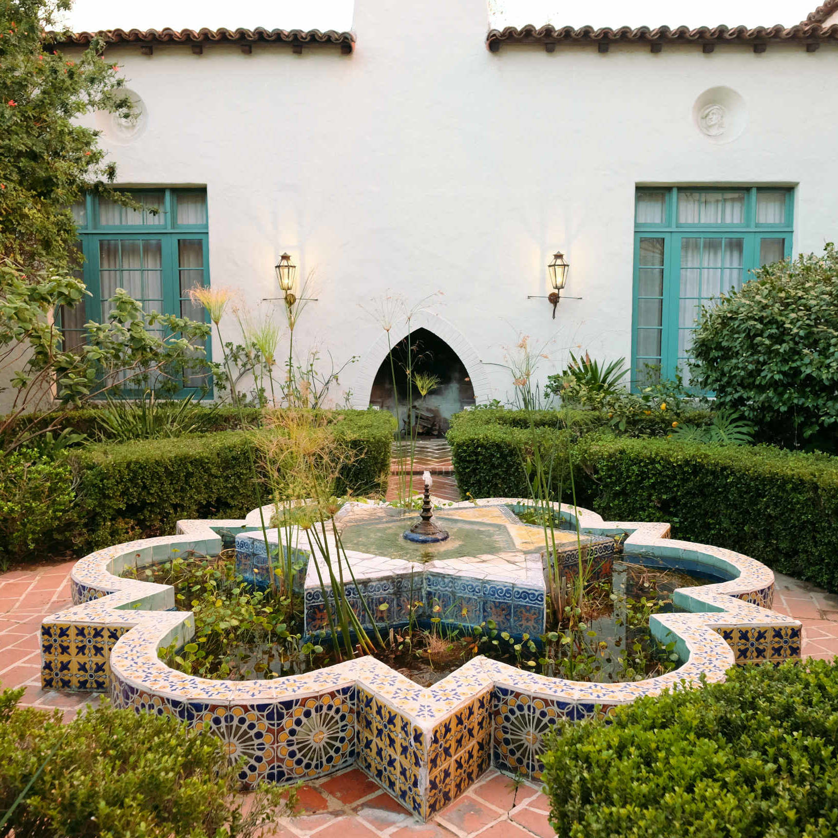 Moroccan tile fountain in Alhambra Apartments courtyard with turquoise windows