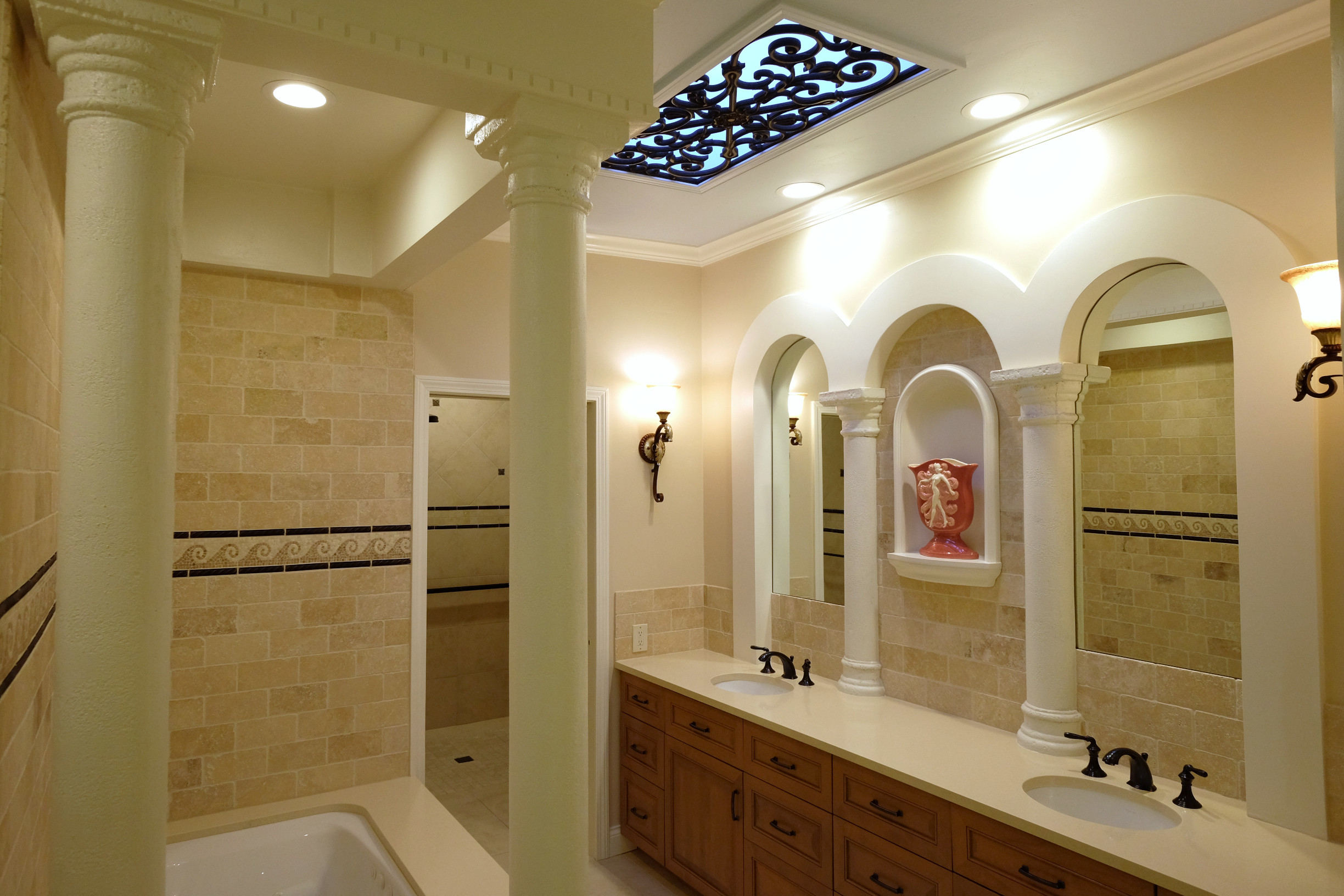 Roman bath with travertine, columns, tile mosaic, and bronze accents